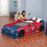 Mom tucking toddler into race car bed