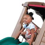 Little girl sliding down the slide of the outdoor swingset for kids