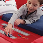 Mom tucking toddler into Corvette twin bed