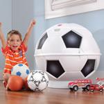 Little boy putting toys in soccer toy bin