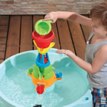 Toddler pouring water into center funnel of play table