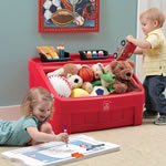 kids putting away toys in red toy chest
