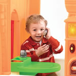 Little boy on toy phone in plastic playhouse for kids