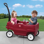 Toddler putting on safety belt in red wagon