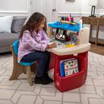 child opening storage area of art desk