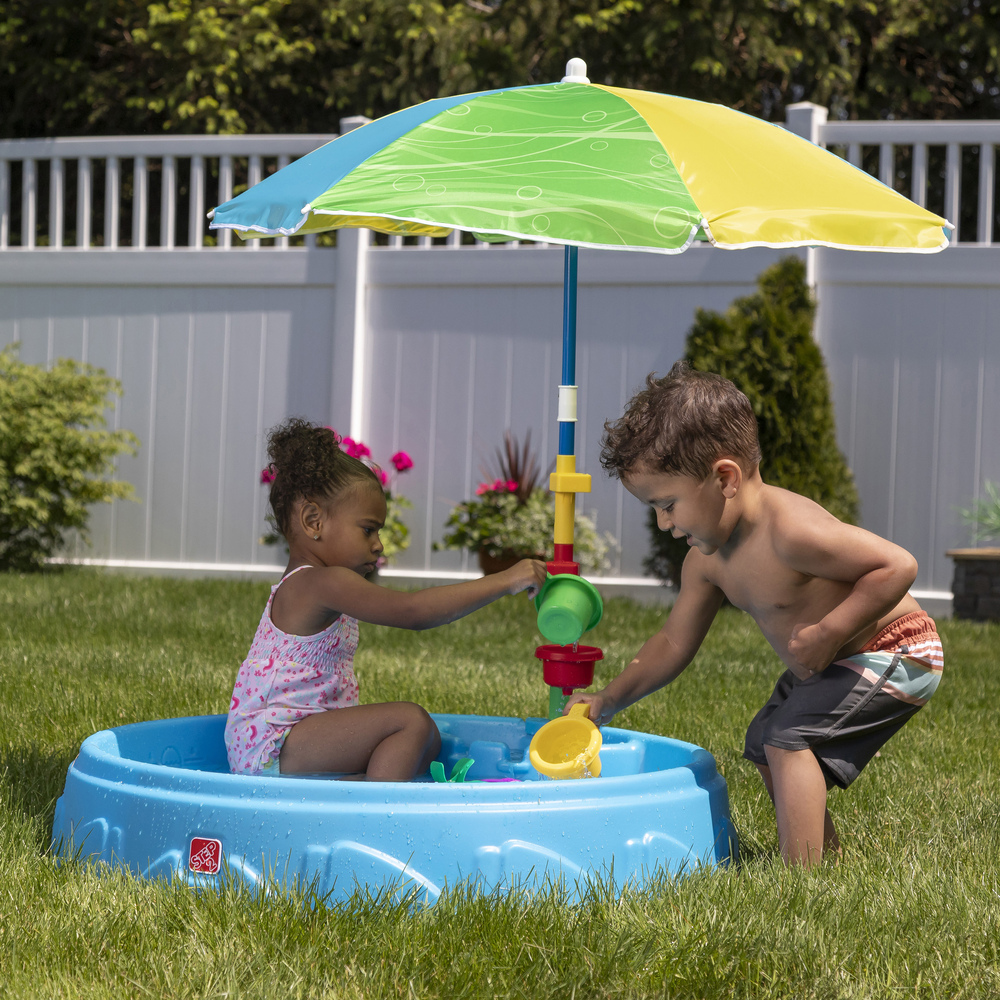 Child pouring water in funnel in kiddie pool