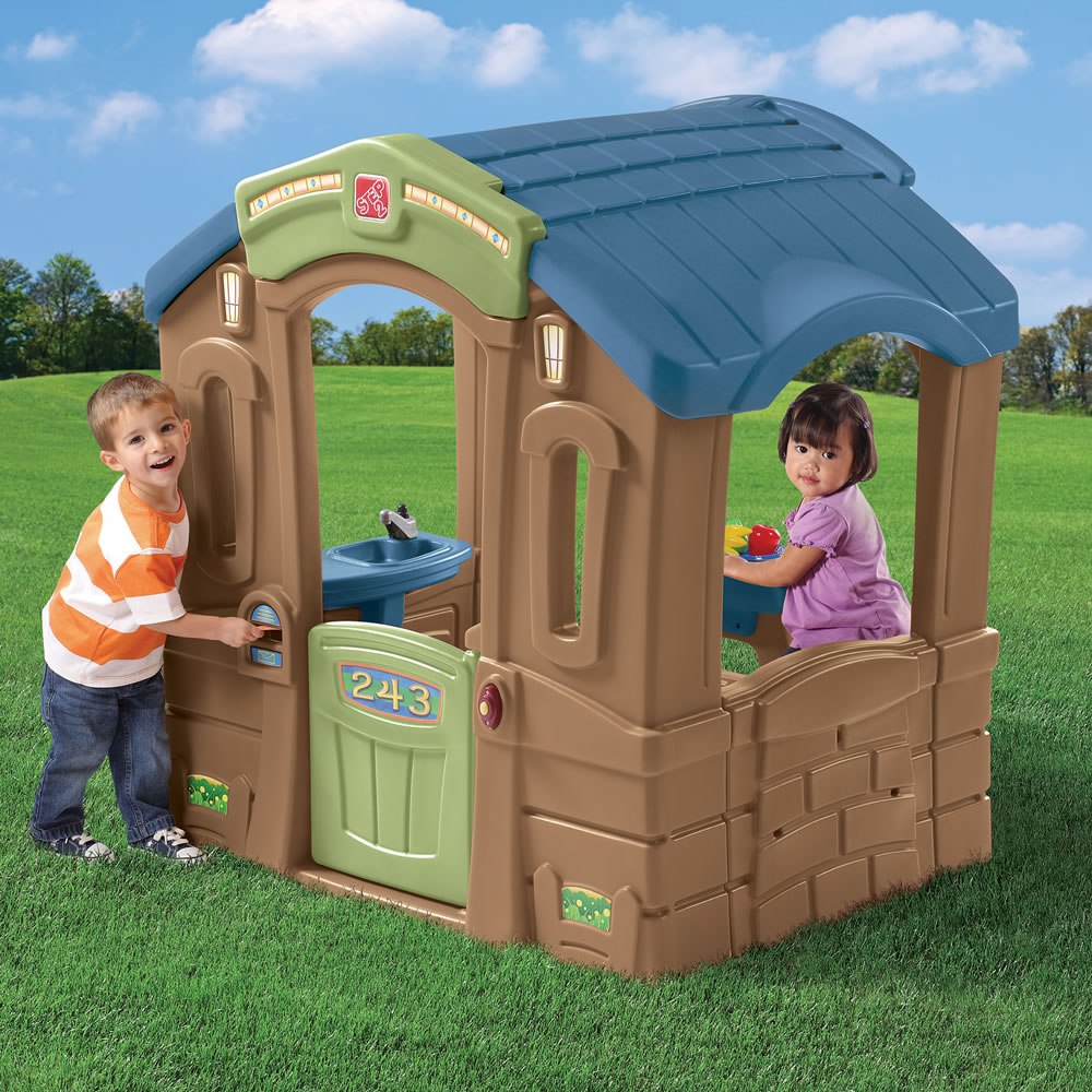 Boy and girl playing in large plastic cottage