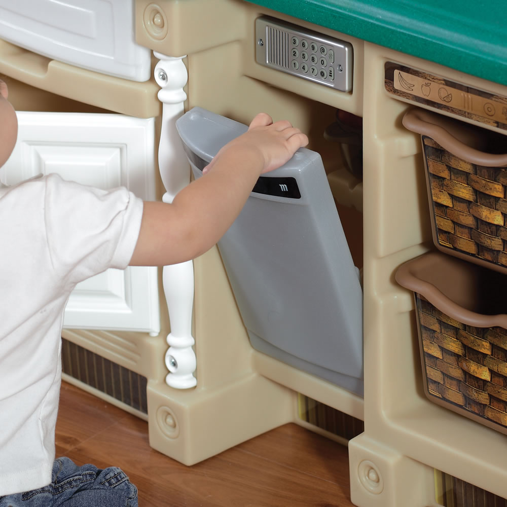 Child putting food into play kitchen oven of Deluxe Kitchen