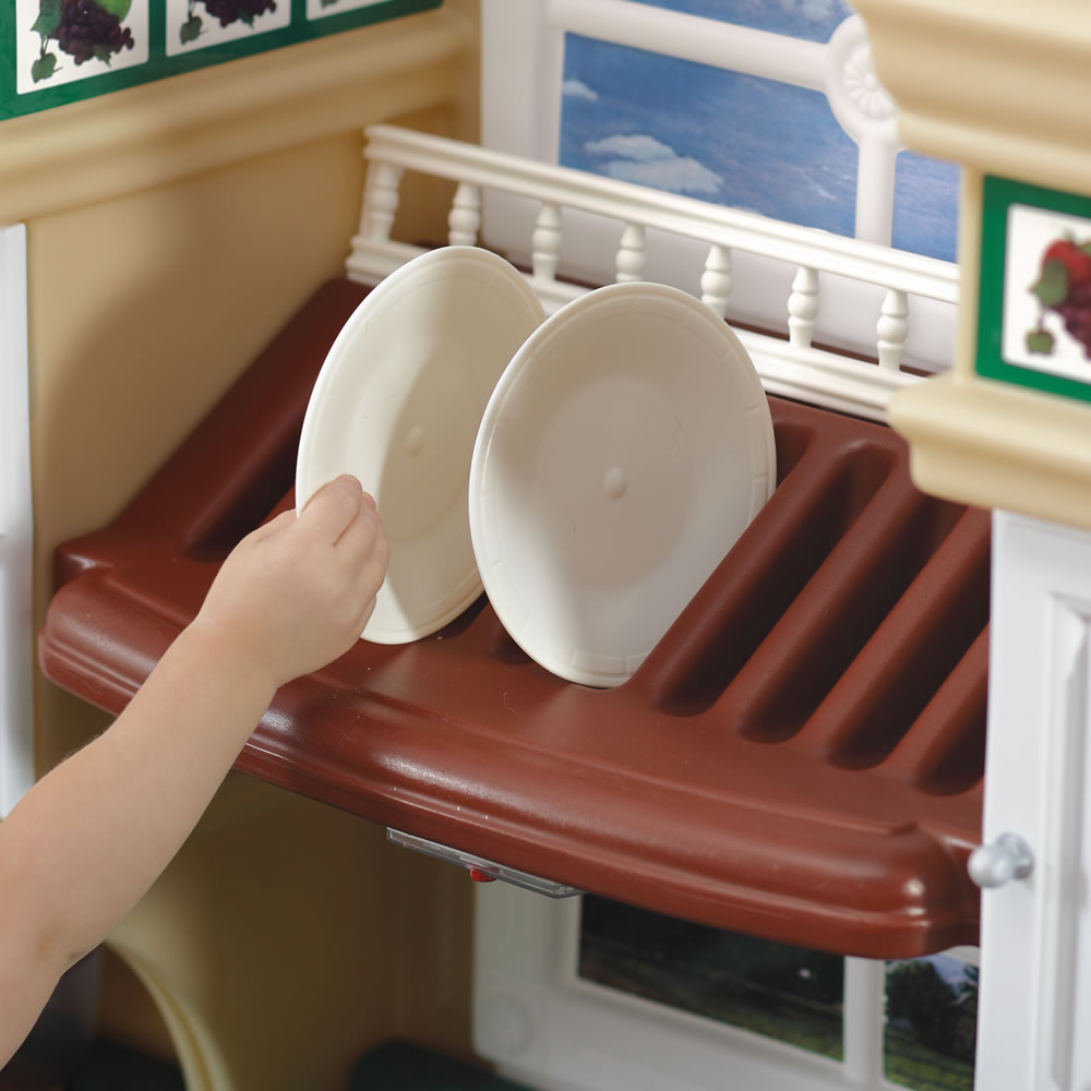 Kid pretending to use play kitchen microwave of Deluxe Kitchen