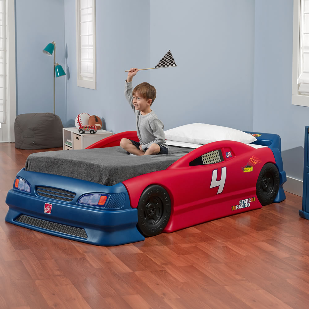 Toddler playing with built in race track on car bed