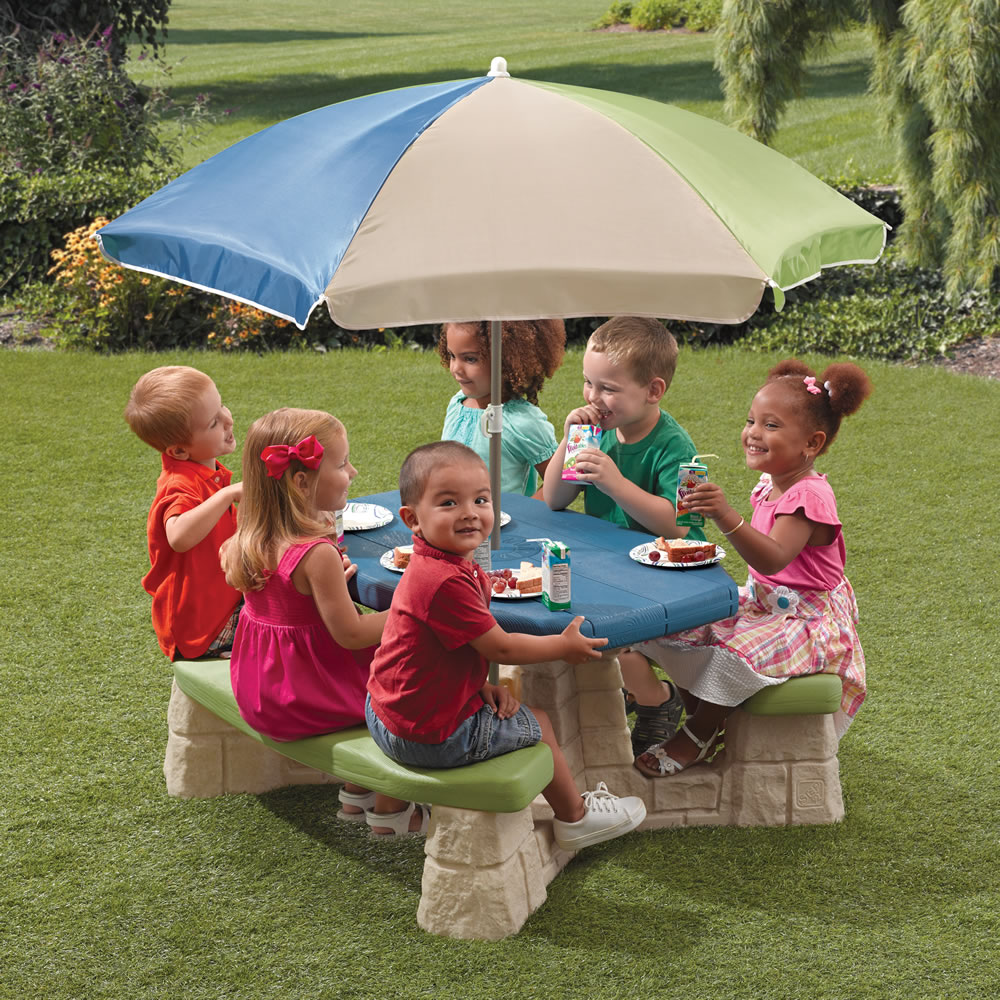 children sitting at plastic picnic table