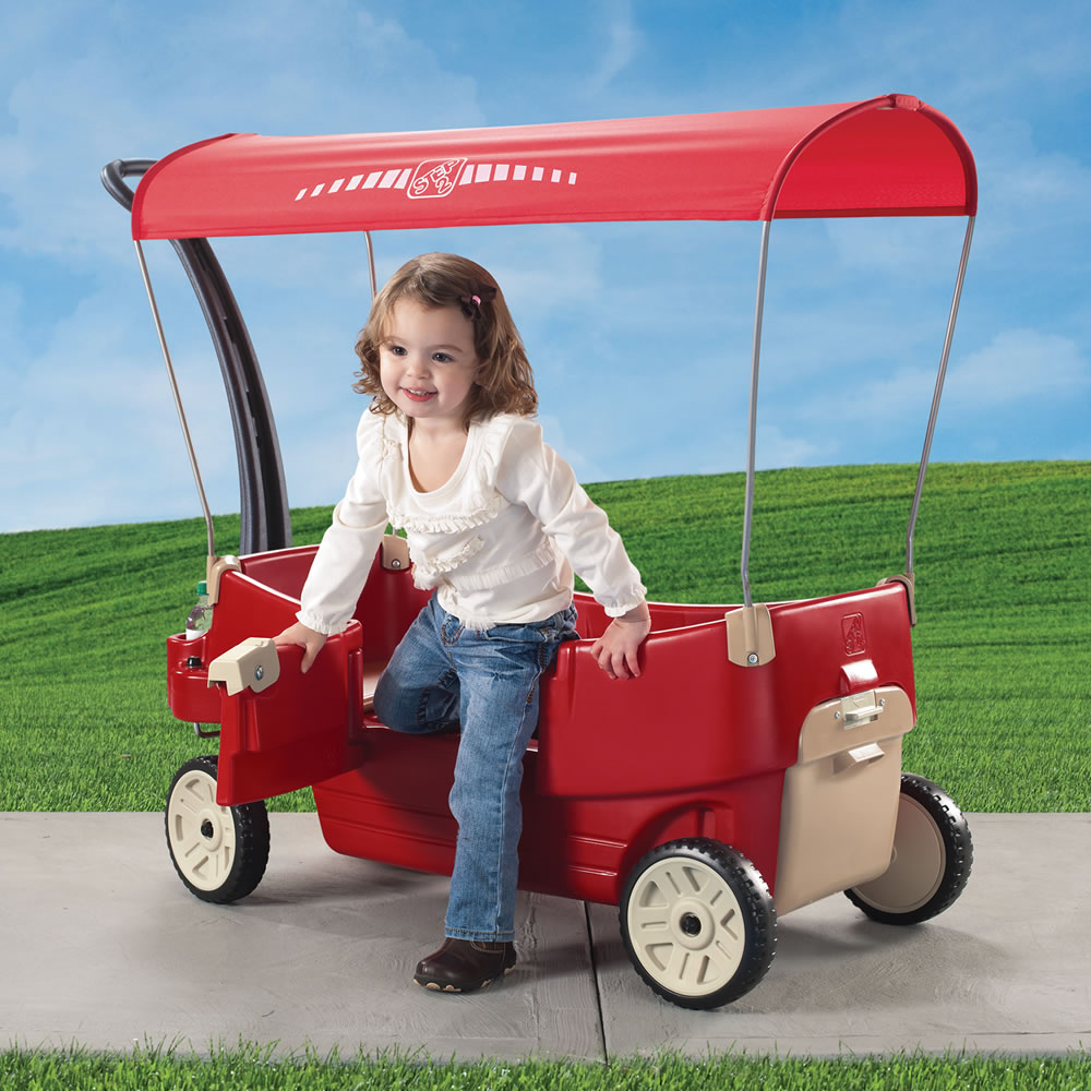Little ones riding in red wagon