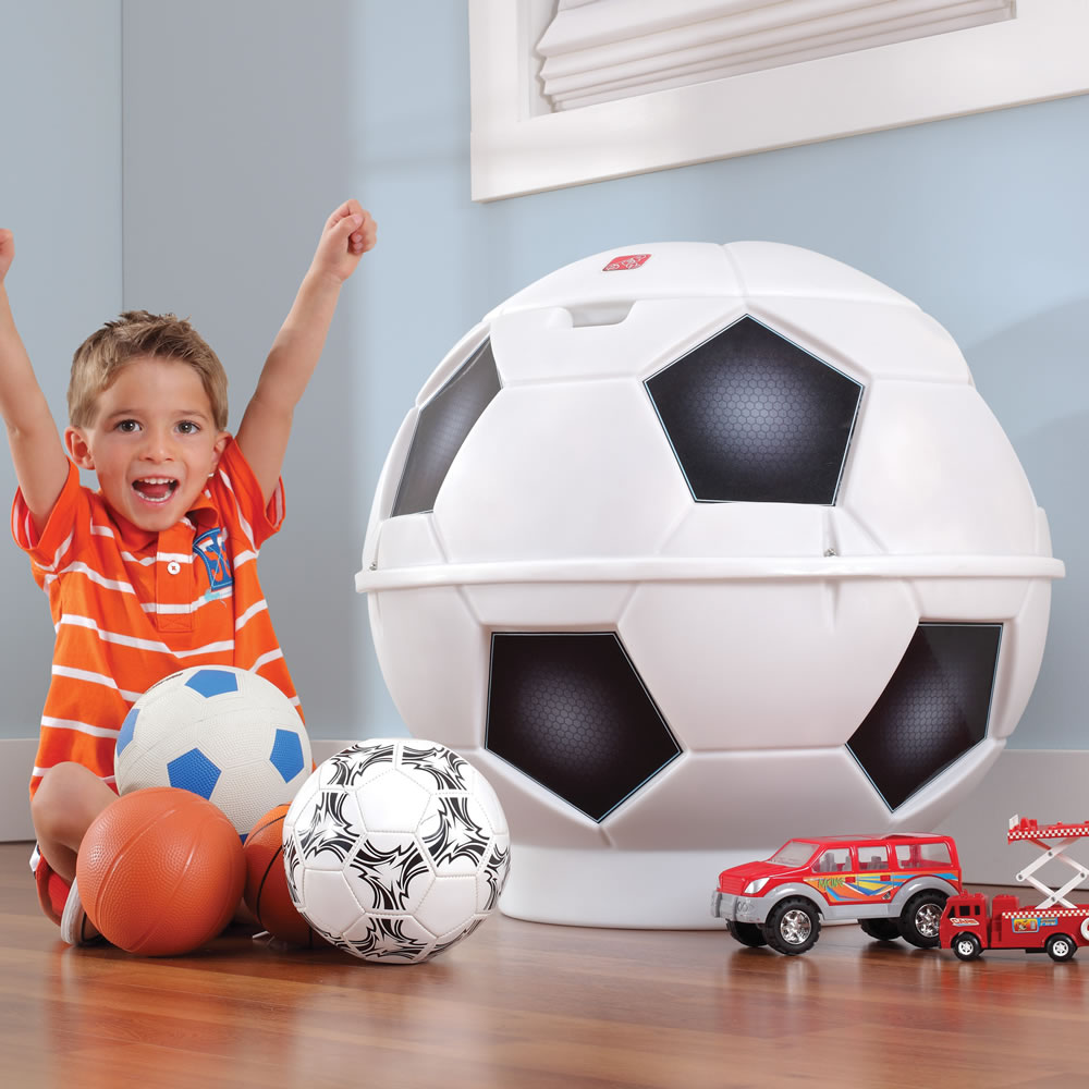 Little boy putting toys in soccer toy bin