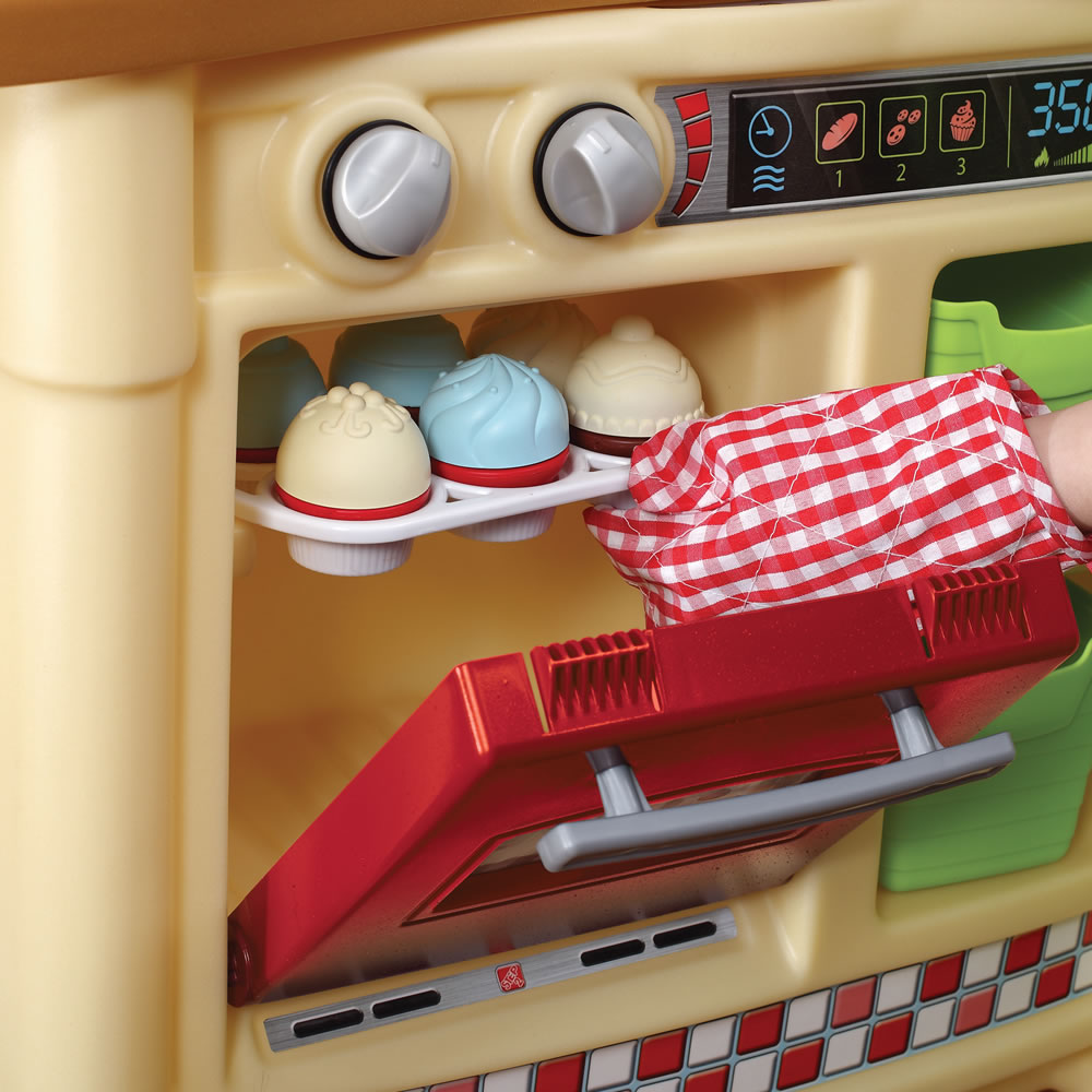 Toddler putting pretend cupcakes in their play kitchen oven