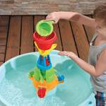 kid pouring water down the funnel of the activity table