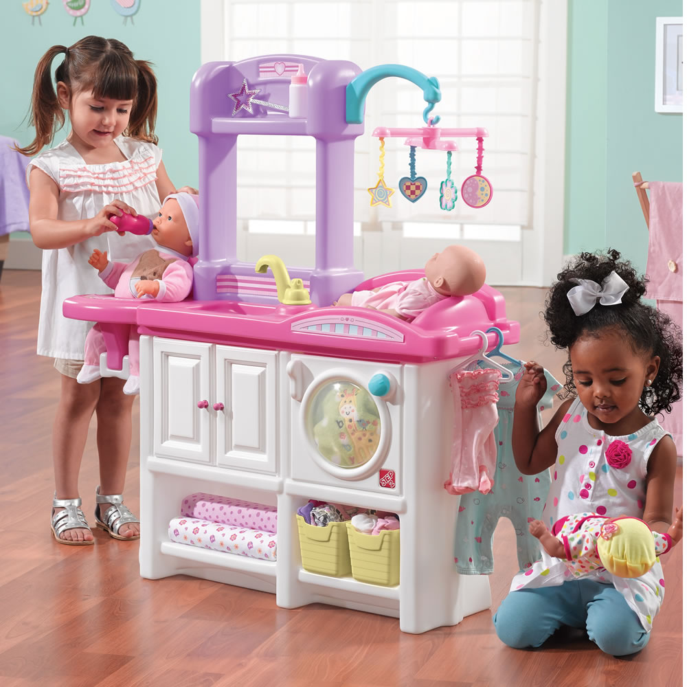 Little girls playing with toy nursery