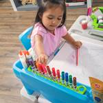 Girl reaching for art supplies on Step2 Deluxe Creative Projects Art Desk