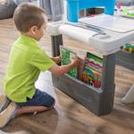 Boy placing coloring book in Step2 Deluxe Creative Projects Art Desk