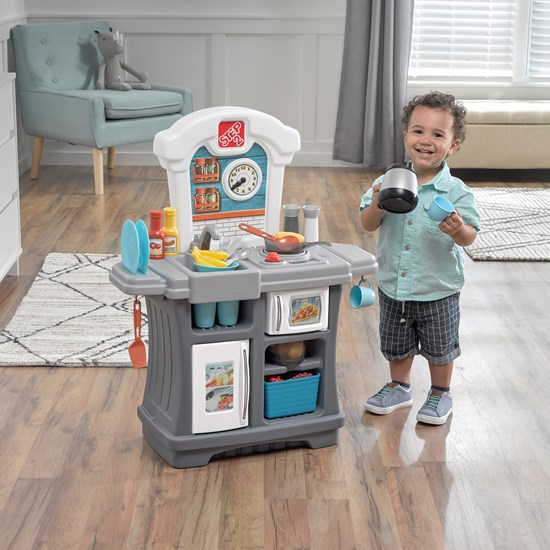 little boy playing with Step2 Kiddos Kitchenette