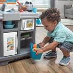 little boy playing with storage in Step2 Kiddos Kitchenette