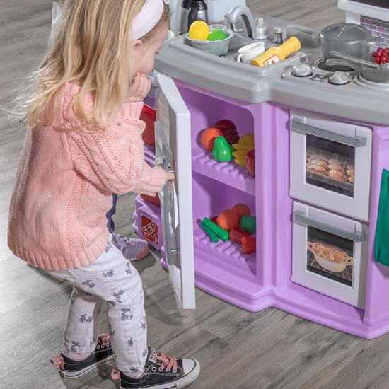 little girl opening refrigerator with step2 great gourmet kitchen lavender