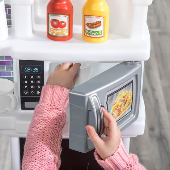 little girl opening microwave with step2 great gourmet kitchen lavender